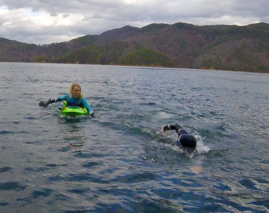 Bellyaking at a safe distance from an open water swimmer